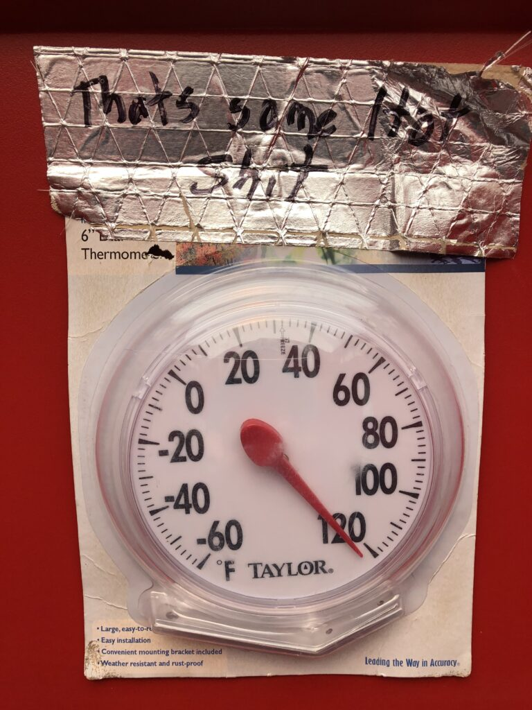 """A thermometer dial from the port-a-potty.  It shows a temperature of more than 120 degrees (the highest it can show).  A construction worker has labelled it with """"That's some hot shit."""""""