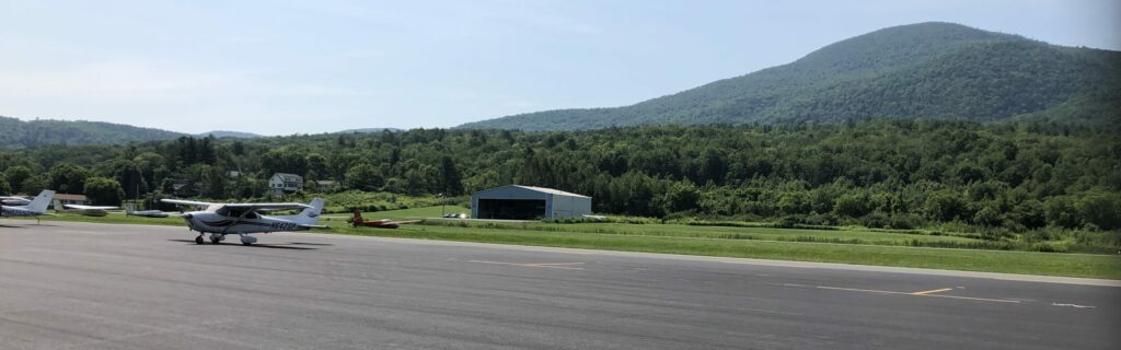 The view from the airport ramp. The airplane is parked in the foreground, with a hanger behind and a tall mountain in the background.