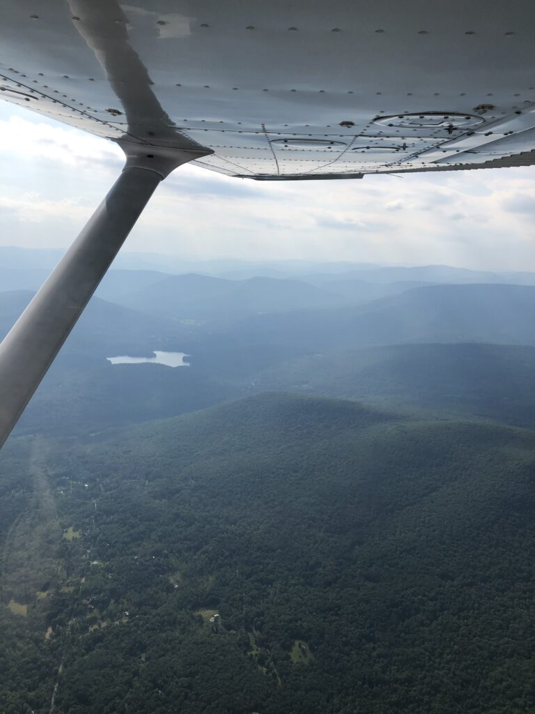 A view out the right of the plane in flight. The Catskill mountains are in view, with a small lake also visible.